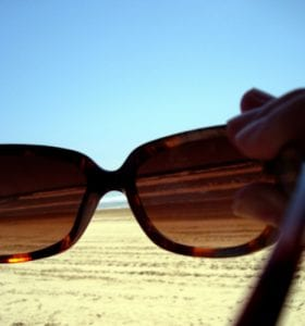 Reading on the beach Sunglasses Visual Q Eyecare South Yarra Melbourne